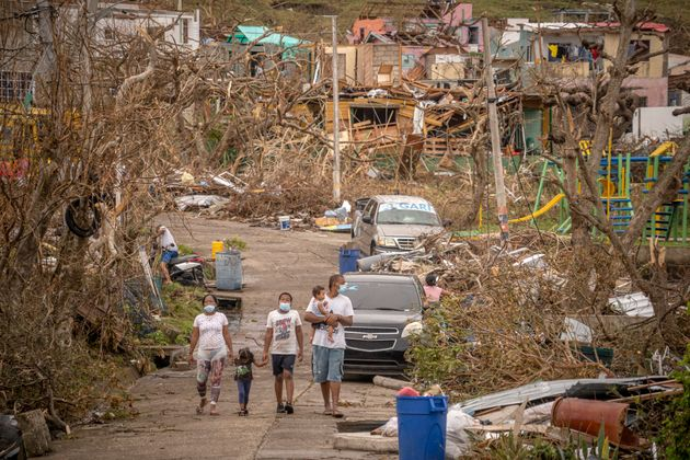 A family walks amid destruction on Nov. 22 in Providencia, Colombia, which was hit by Hurricane Iota...