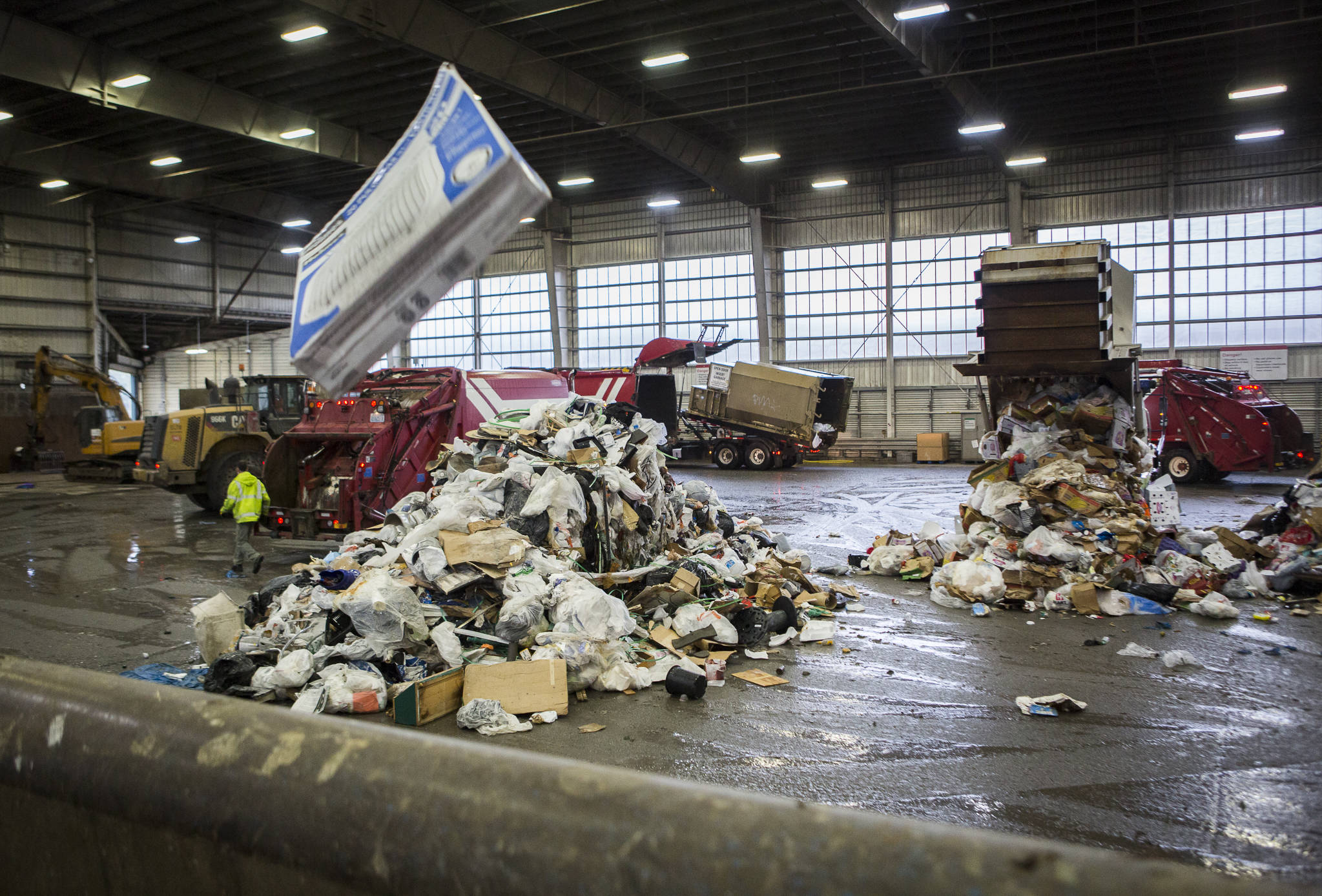 Garbage trucks dump trash onto the tipping floor at the Airport Road Recycling & Transfer Station on Nov. 24 in Everett. Photo by Olivia Vanni/The Herald (Everett)