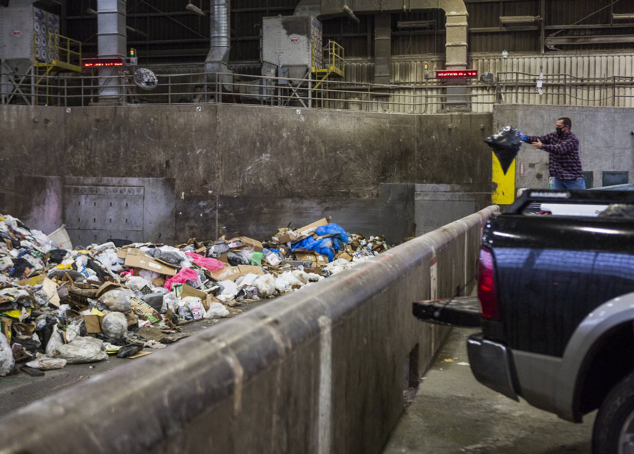 People throw their trash onto the tipping floor to be loaded into a compactor at the Airport Road Recycling & Transfer Station on Nov. 24 in Everett. Photo by Olivia Vanni/The Herald (Everett)
