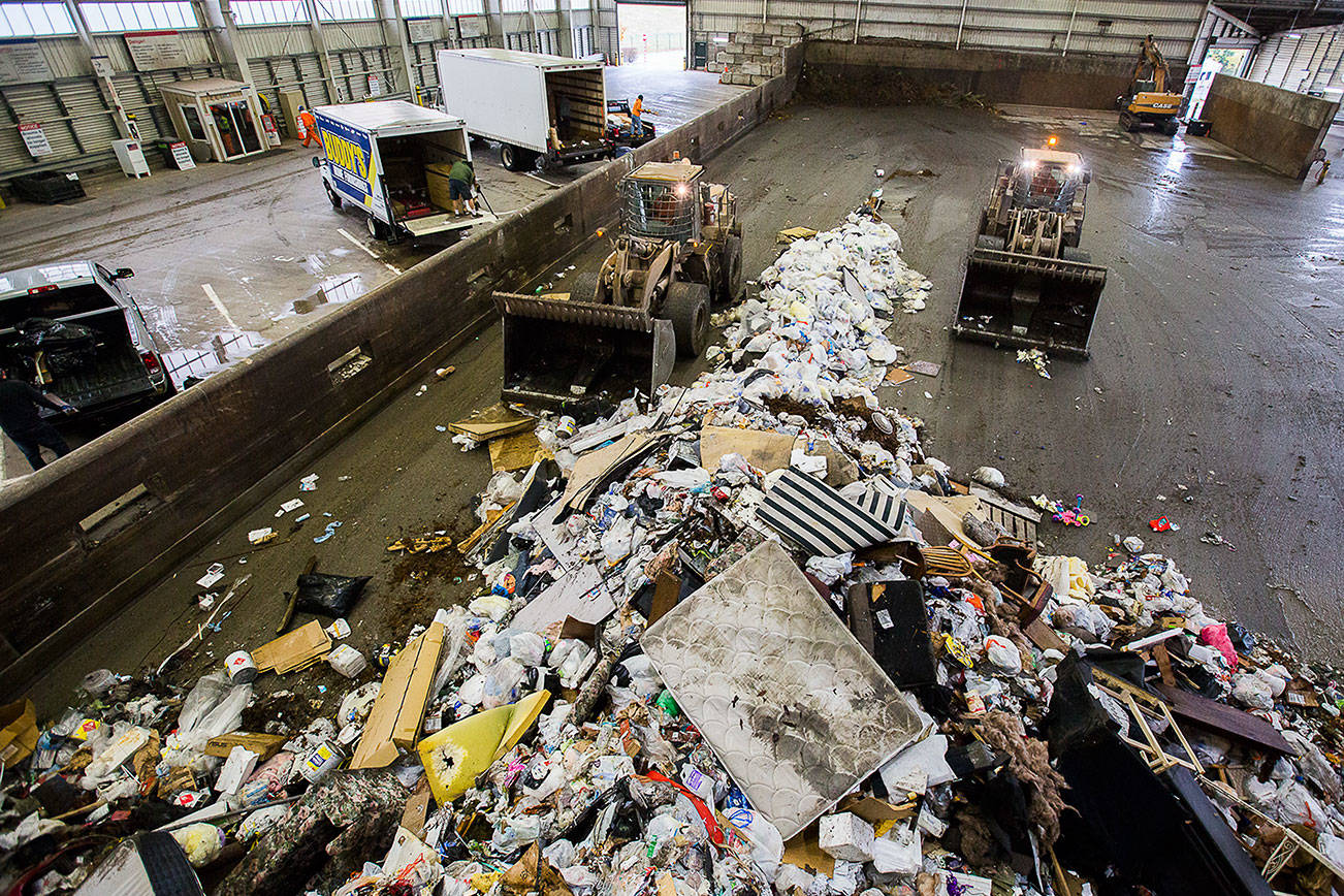 Front loaders push trash forward into one of the compactors at the Airport Road Recycling & Transfer Station on Tuesday, Nov. 24, 2020 in Everett, Wa. (Olivia Vanni / The Herald)
