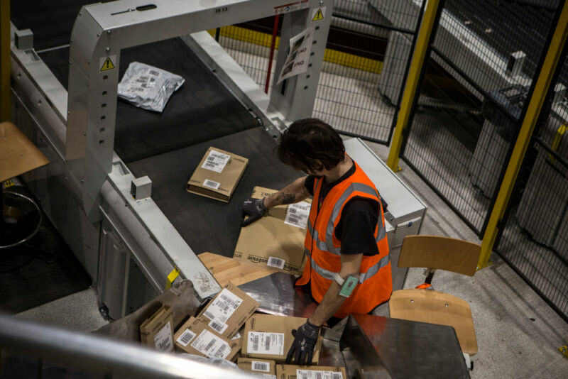 A man in an orange vests moves Amazon packages on a conveyor belt.