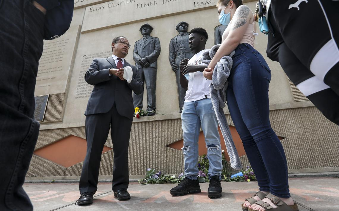 From left: Minnesota Attorney General Keith Ellison explains the Duluth lynchings that took place in 1920 and the recent pardoning of Max Mason to Abdulahi Hussein, Tawny Worsley and Kirsten Kelly at the Clayton Jackson McGhie Memorial Monday, June 15, 2020. (Tyler Schank / tschank@duluthnews.com)