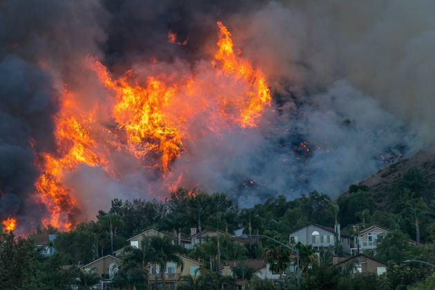 Flames rise near homes during the Blue Ridge fire on Oct. 27 in Chino Hills,