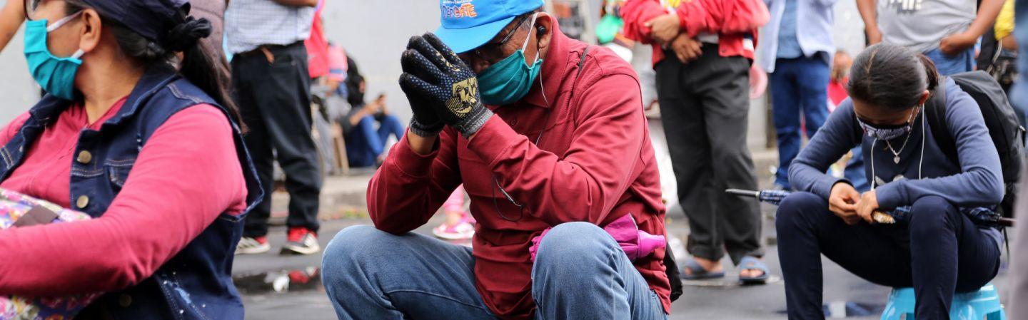 Peruvians wearing masks to protect themselves from COVID-19 wait outside a bank to collect government aid bonuses in Iquitos, Peru, on June 15, 2020.