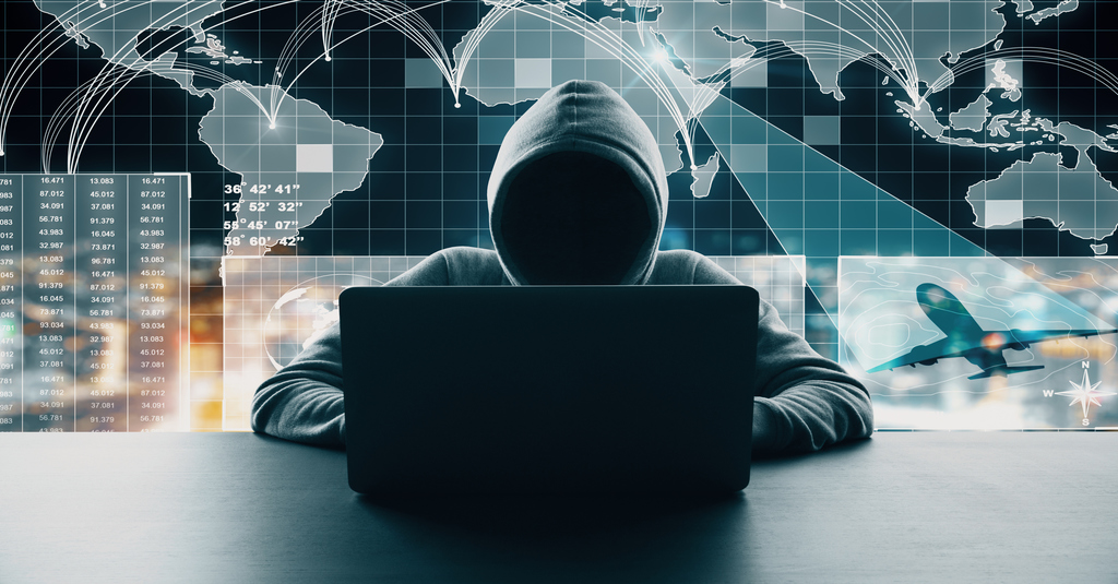 Dark Web danger represented by a hacker in a hoodie hunched over a black computer in front of a glowing world map to advise your cybersecurity new year's resolutions