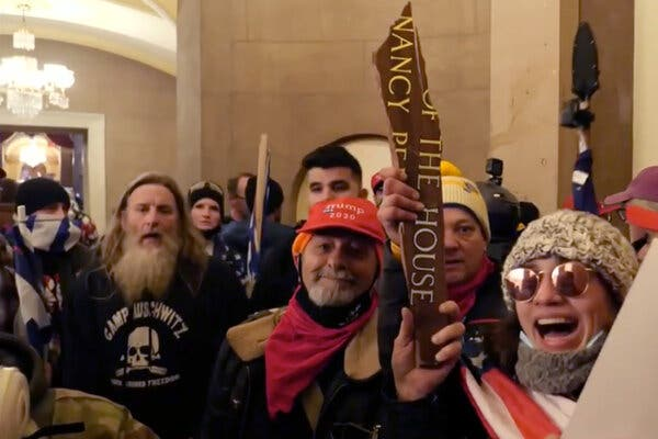 "One of the rioters, at left, who broke into the Capitol was wearing a hoodie emblazoned with ""Camp Auschwitz."""