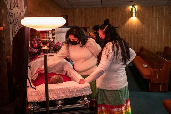 On the Standing Rock Reservation in North Dakota, four Lakota elders from one family have died in the pandemic, including the parents of Jessie Taken Alive-Rencountre, right, and her sister Nola Taken Alive, who placed a bundle of sage in their mother's coffin.