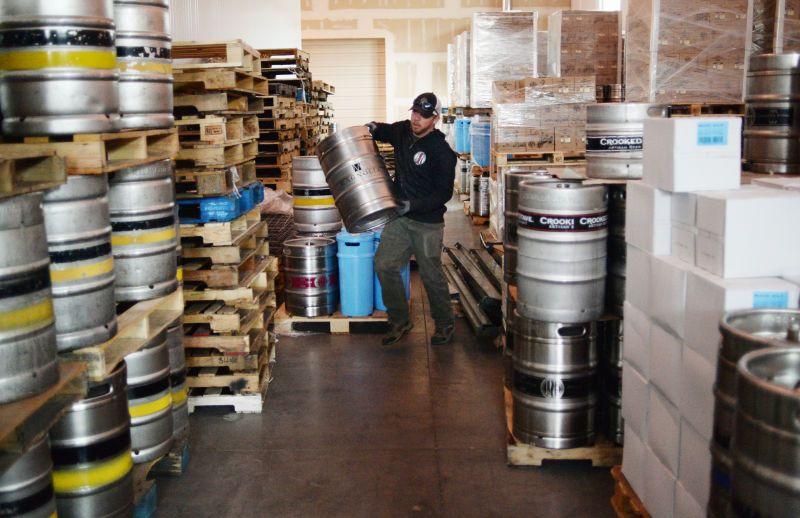 Delivery man stacks kegs of beer