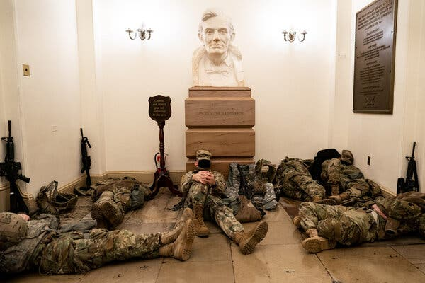 National Guard members resting in the Capitol on Wednesday near a plaque commemorating troops quartered there during the Civil War.