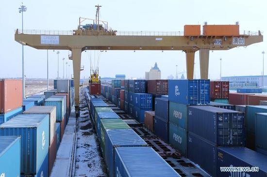Photo taken on Jan. 5, 2021 shows a gantry crane lifting a container in Manzhouli, north China's Inner Mongolia Autonomous Region. The number of China-Europe freight trains arriving and departing via Manzhouli, China's largest land port, reached a record high in 2020 despite the impact of COVID-19, local railway authorities said Wednesday. (Photo by Guo Nailun/Xinhua)