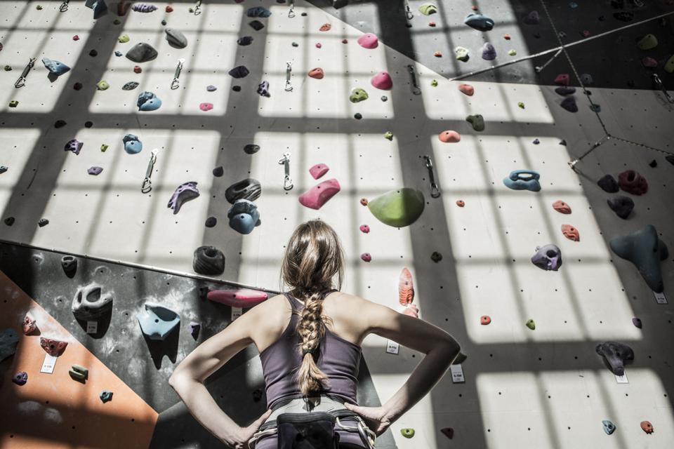 Athlete examining rock wall in gym