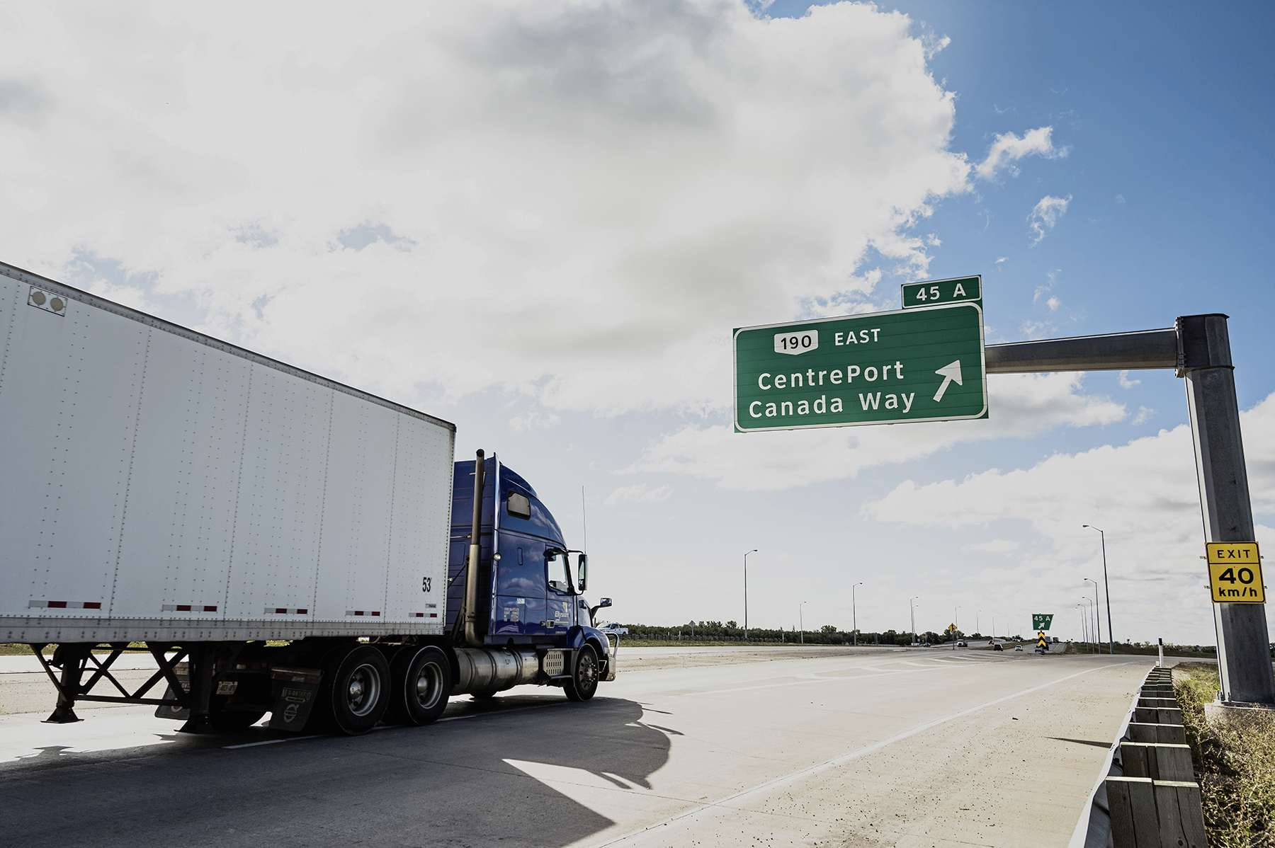 A semi passing a sign pointing to CentrePort Canada Way.