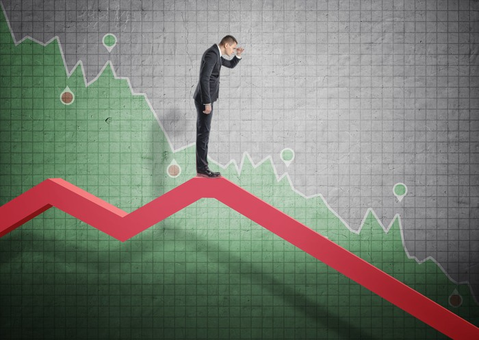 Man standing on a downward-bound graph.