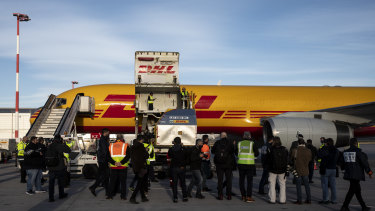 A shipment of Pfizer-BioNTech Covid-19 vaccines is unloaded from a DHL Worldwide Express cargo plane at Athens International airport, in Athens, Greece.
