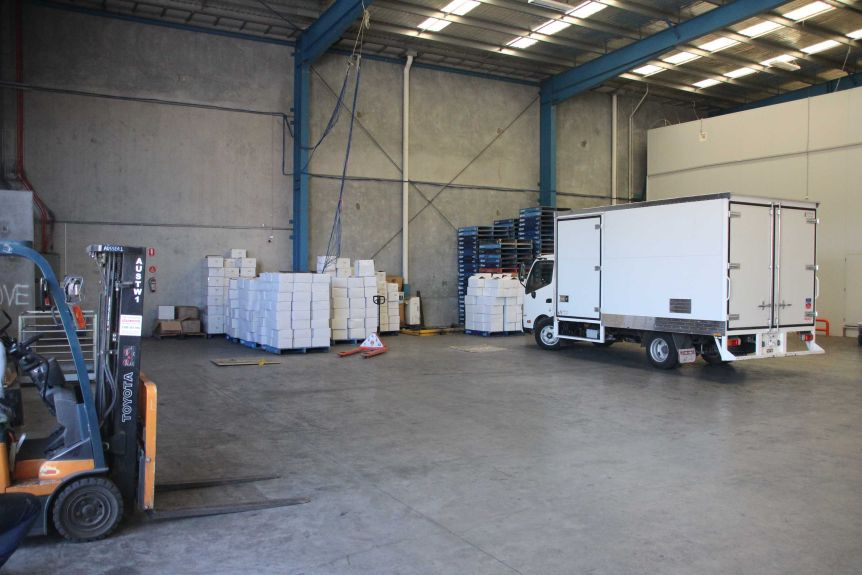 A truck in a warehouse with several stacked white boxes.