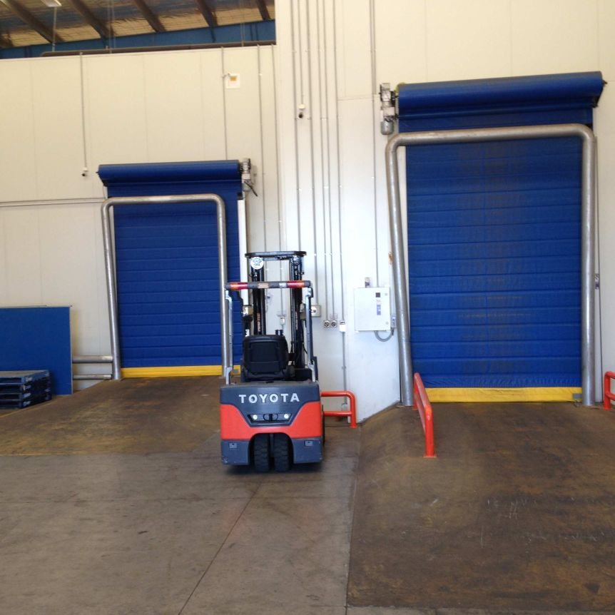 A forklift in a warehouse between two roller doors.