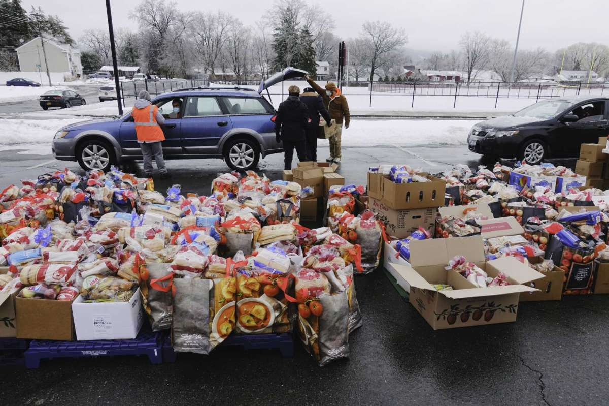 A mass food distribution takes place Friday, Feb. 26, 2021 at Macedonia Baptist Church at 26 Wilson Ave. in Albany. In this photo, volunteers load food bags and boxes into vehicles during a previous mass food distribution put on by Catholic Charities of the Diocese of Albany, and the Regional Food Bank of Northeastern New York on Tuesday, Feb. 16, 2021, at Watervliet High School in Watervliet, N.Y. (Paul Buckowski/Times Union)