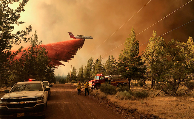 A firefighting tanker makes a retardant drop over the Grandview Fire near Sisters, Ore.